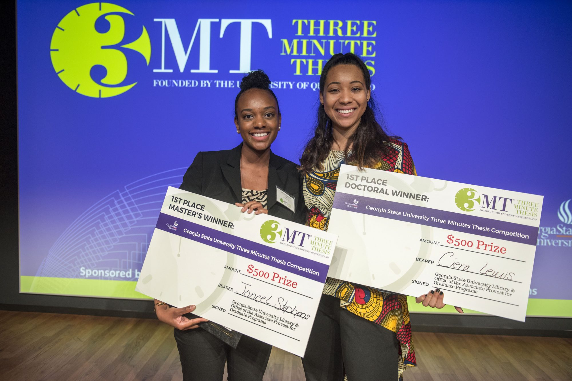 2018 First Place 3MT Winners on stage with Awards